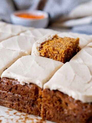 A slice of spiced carrot cake peeking out of the sheet cake