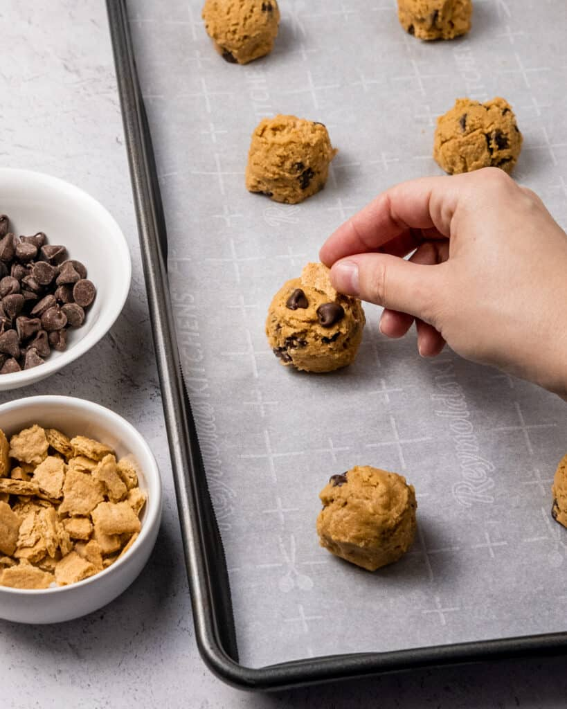 placing chocolate chips and graham crackers on cookie dough