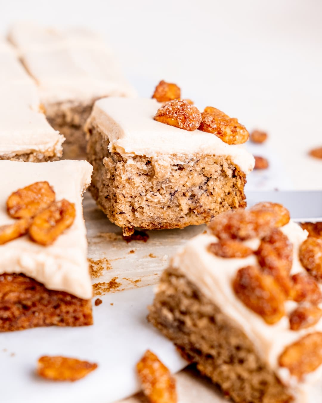 a slice of banana snack cake with frosting and honey glazed peanuts on top