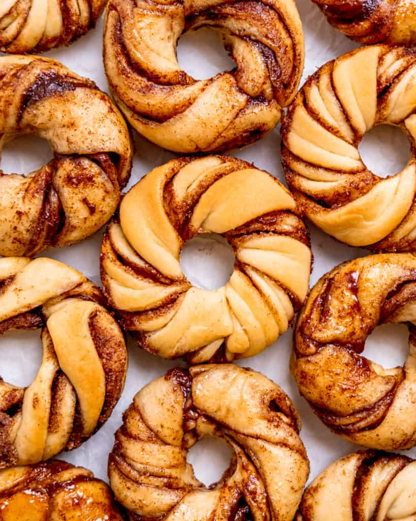 Cinnamon roll donuts laying next to each other on white parchment paper