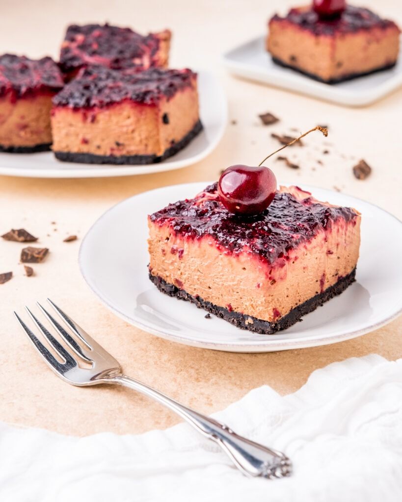 a slice of chocolate cherry cheesecake with a cherry on top, sitting on a white dessert plate with a fork next to it