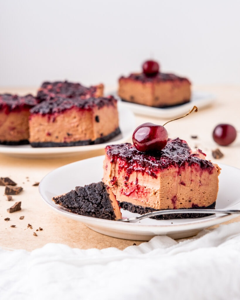 A slice of chocolate cherry cheesecake with a cherry on top and a bite taken out with a fork that's laying on the plate with it