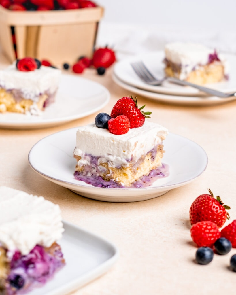 A slice of milk and berries cake on a white plate with a strawberry, raspberry, and blueberry on top of the whipped cream frosting.
