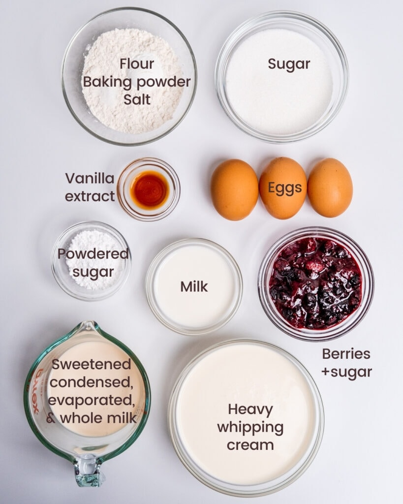 Ingredients for the milk and berries cake laid out on a white background