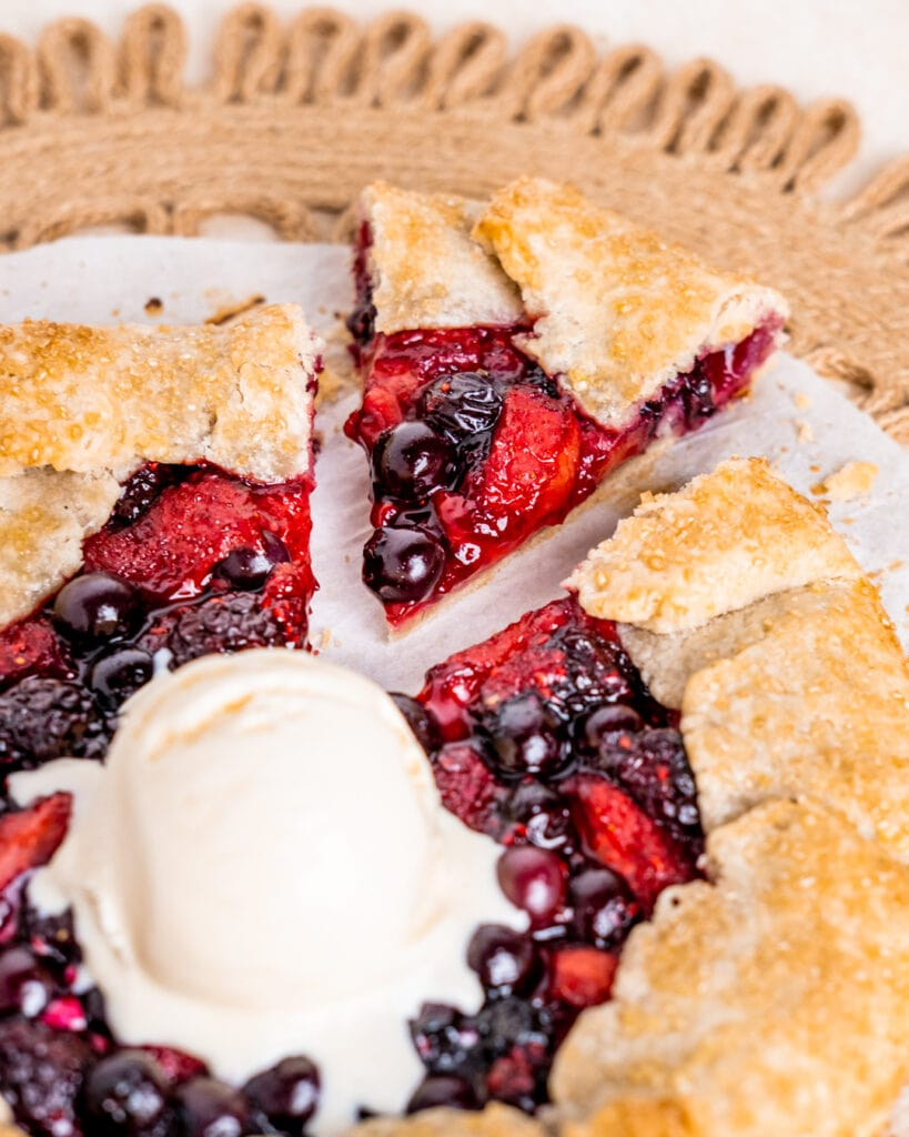 Mixed Berry Galette with a scoop of vanilla ice cream and a triangle slice cut out