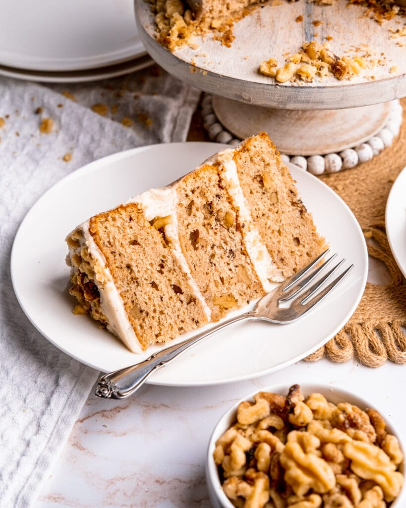A slice of spiced walnut cake sitting on a white dessert plate with a silver fork