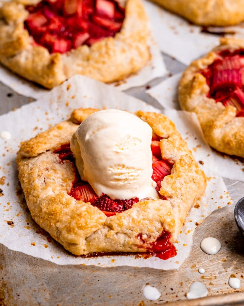 a mini strawberry rhubarb galette with a scoop of vanilla ice cream on top
