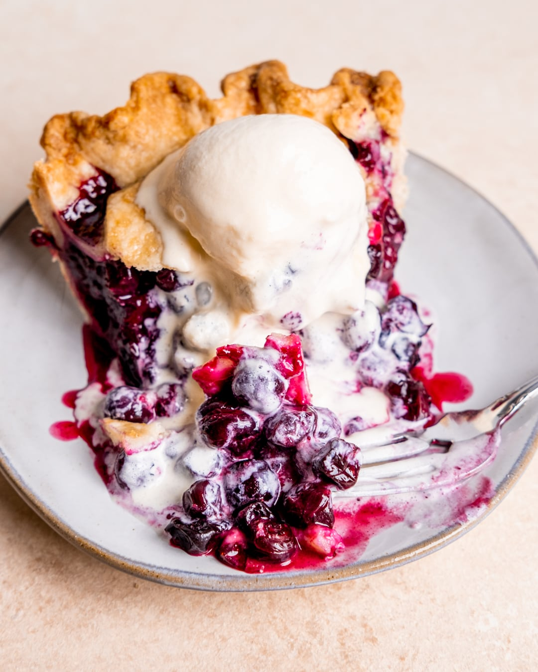 A bite cut out of blueberry pie with a scoop of vanilla ice cream melting on top