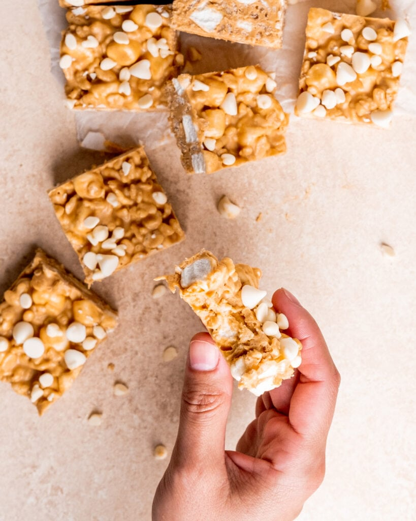 A hand holding a chocolate peanut butter rice krispie treat that has a bite taken out of it