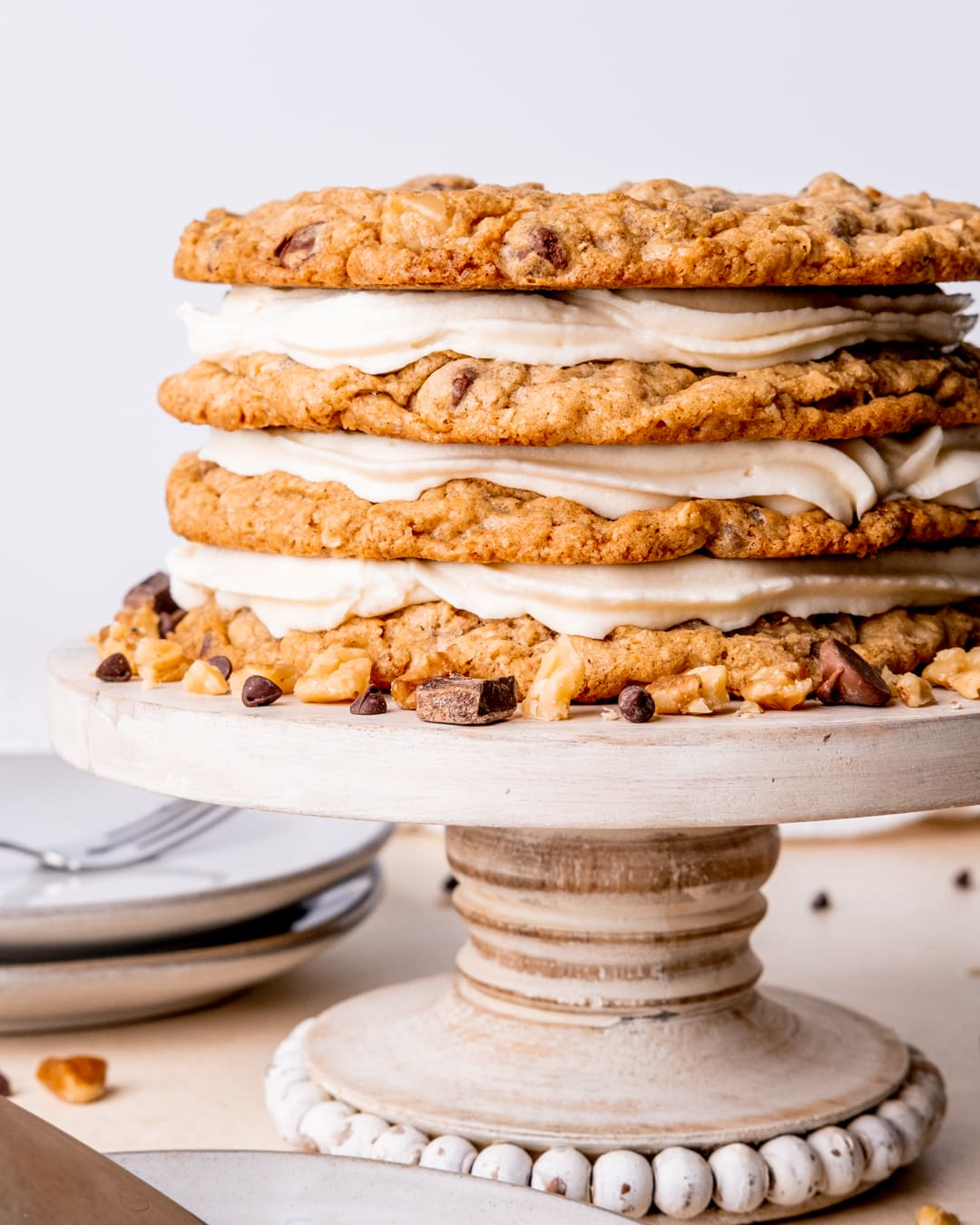 a cowboy cookie cake on a cake stand with chocolate chips and walnuts around it