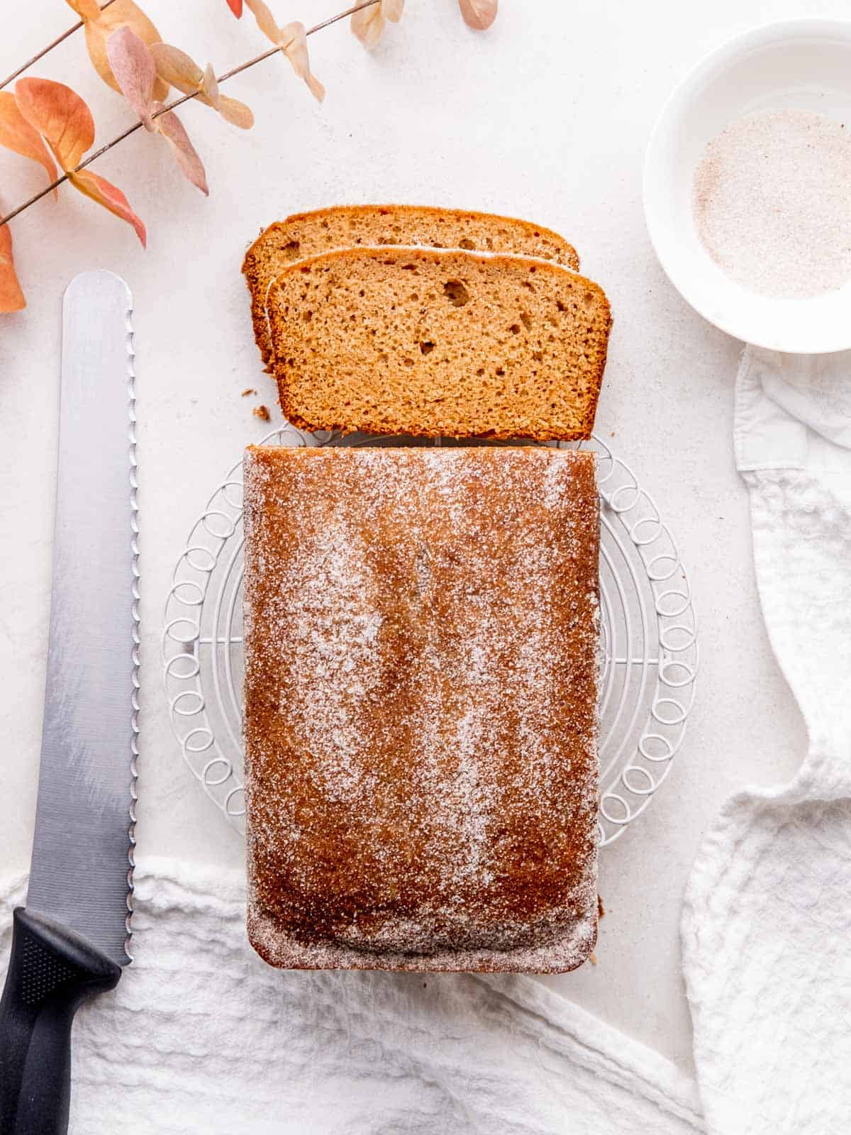 Top view of the apple cider loaf cake topped with chai sugar. Two slices are cut and laying next to the loaf.