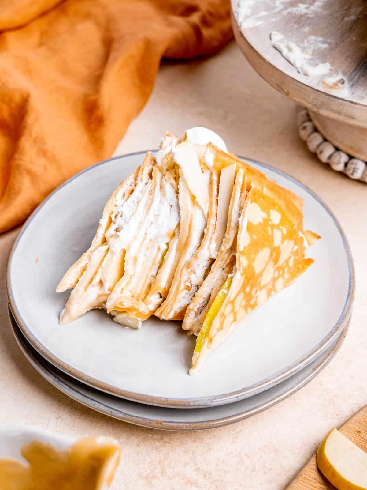 a slice of caramel apple crepe cake on a plate