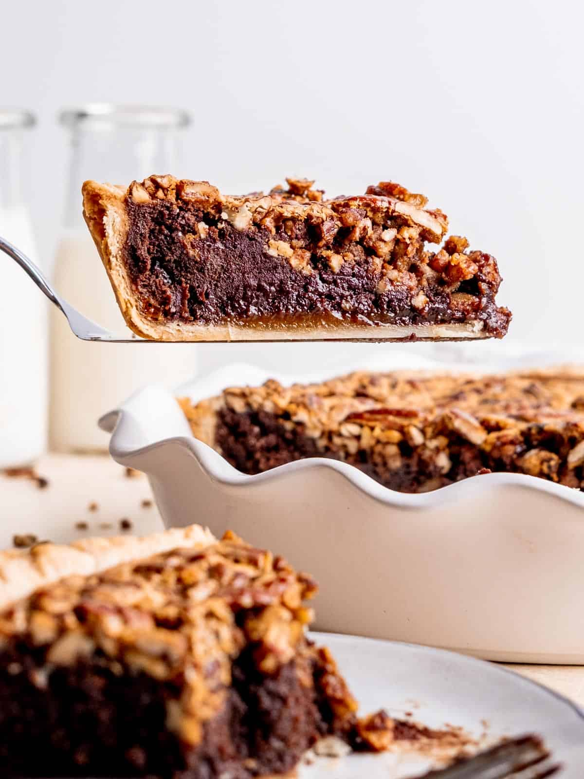 a slice of pecan brownie pie being lifted out of the pie dish