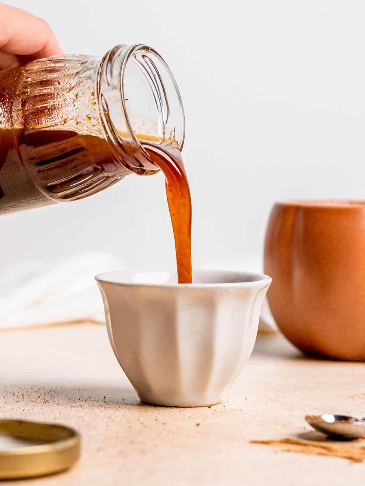 Pouring pumpkin spice syrup from a small glass jar into a tiny ceramic bowl