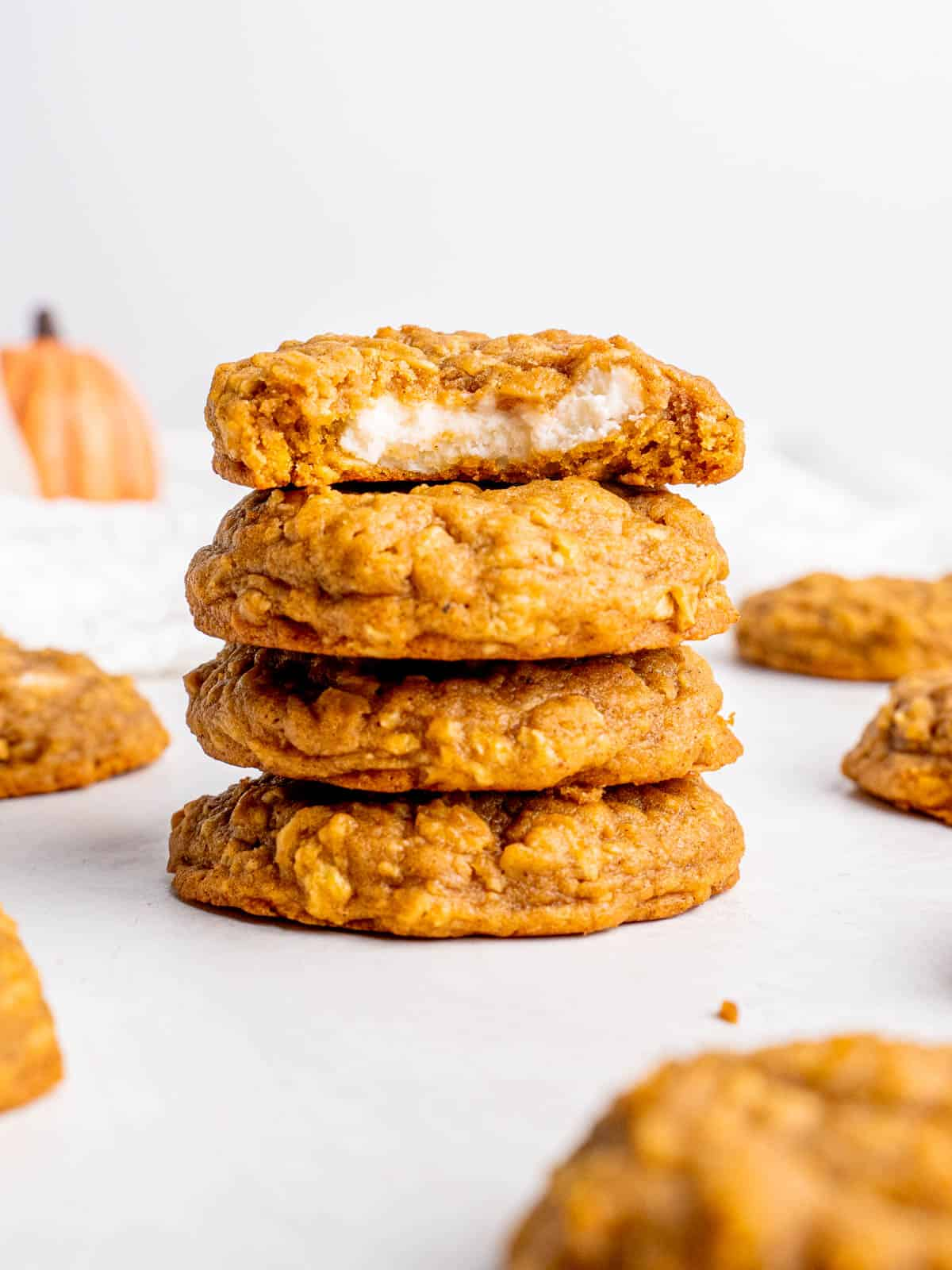 a stack of oatmeal pumpkin cheesecake cookies with the top one cut in half revealing the filling