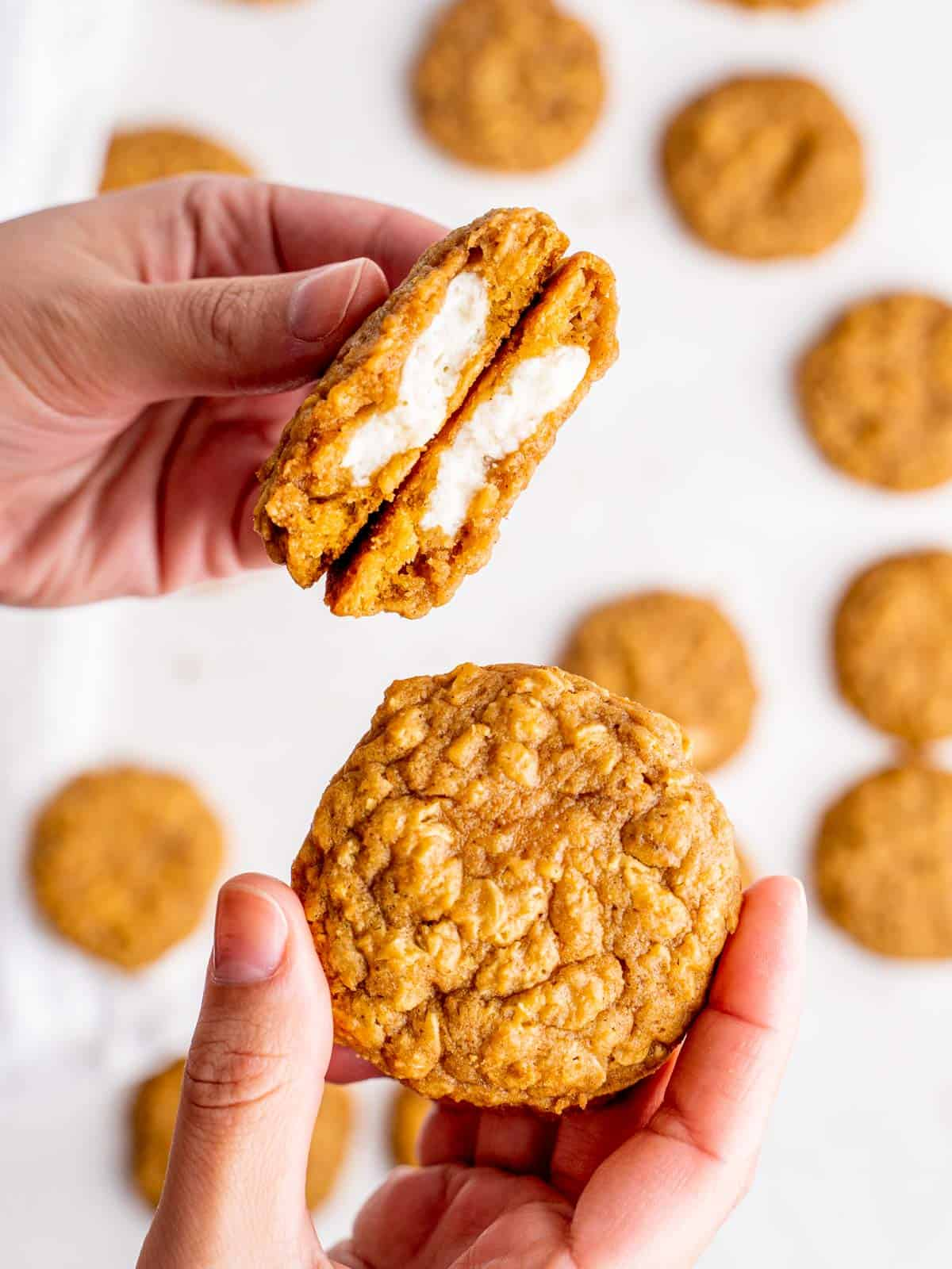 one hand holding two halves of an oatmeal pumpkin cheesecake cookie showing the center and one hand holding a whole cookie